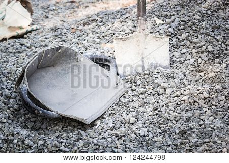 clam-shell shaped basket black with a scoop shovel beside the stone to the concrete mix.