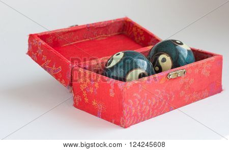 Two blue ying - yang metal balls in red box for relaxation and meditation