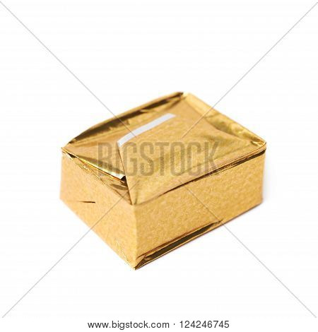 Single bouillon stock broth cube wrapped in golden foil, composition isolated over the white background ** Note: Shallow depth of field