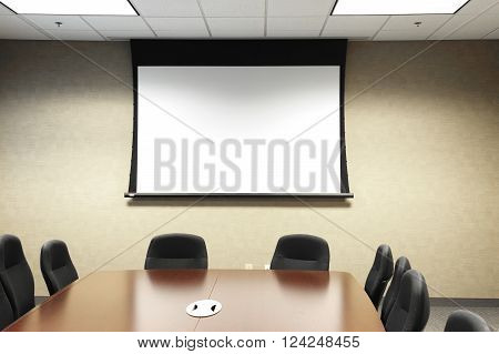 table, chairs in meeting room with projector screen