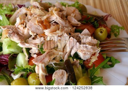 Mixed vegetable salad with chicken meat on a white bowl.