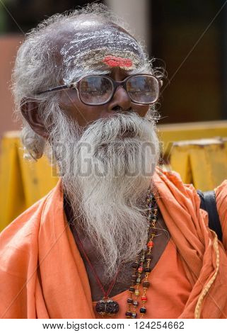 Trichy, India - October 15, 2013: Old, graying sadhu with beard and glasses. Wears orange garb and has his forehead smeared with white and red. Seen in Anna Mandapam.