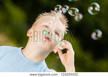 Close up on happy little blond boy with spiked hair and blue shirt blowing bubbles upward from green wand outdoors