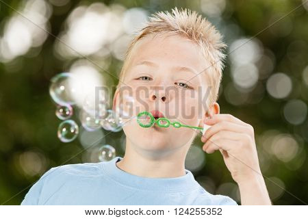 Close up of cute little blond boy with spiky hair and blue shirt blowing bubbles from green wand outdoors