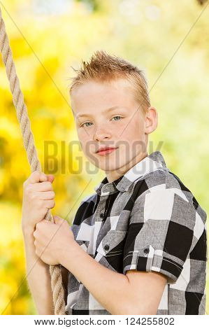 Young Boy Clutching A Rope Outdoors In The Garden
