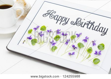 Happy Birthday greeting card - handwriting with viola flowers and leaves on digital tablet with a cup of coffee