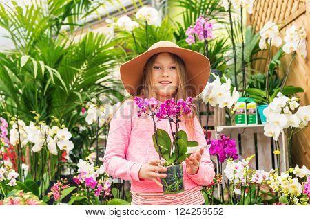Adorable little girl choosing orchid flowers in garden center