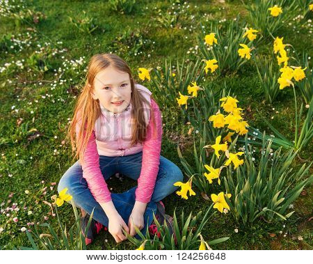 Spring portrait of a cute little girl of 8-9 years old, having fun outdoors, playing with flowers