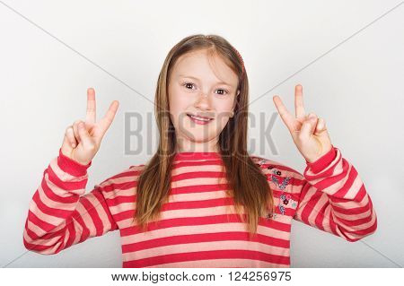 Studio portrait of adorable little girl of 8-9 years old, wearing coral color stripes pullover, standing against white background, showing peace sign