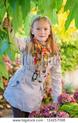 Outdoor portrait of a cute little girl of 8 years old, wearing beige coat and colorful scarf
