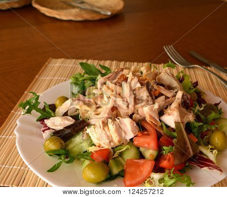 Mixed vegetable salad with chicken meat on a white bowl