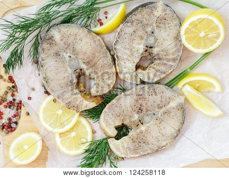 Raw sliced steaks of sturgeon with lemon dill and spices
