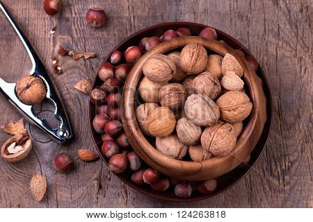 Walnuts and hazelnuts with a nutcracker on rustic wooden background