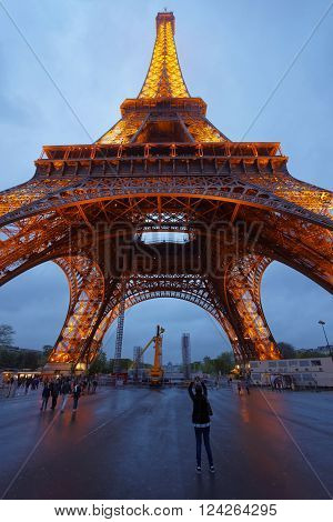 PARIS FRANCE -MAY 2 2012: Illuminated Eiffel Tower in Paris France in the evening. Eiffel Tower is an iron lattice tower on the Fields of Mars of Paris. It is a cultural icon for France