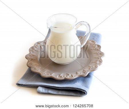 A jar of milk on a plate and napkin isolated on white