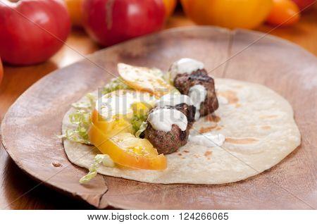 ground lamb on handmade tortilla flatbreads with heirloom tomato and tzatziki