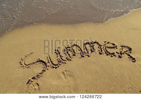 Word summer handwritten in sand on the beach next to the waterline
