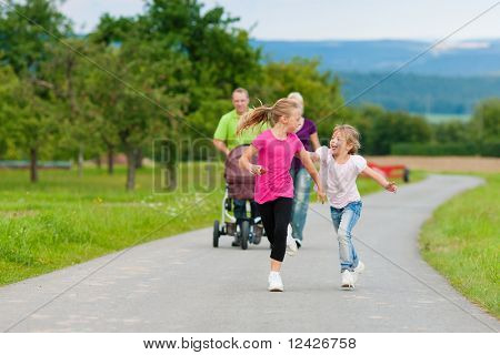 Family with three children (one baby lying in a baby buggy) walking down a path outdoors, the two older daughters running ahead
