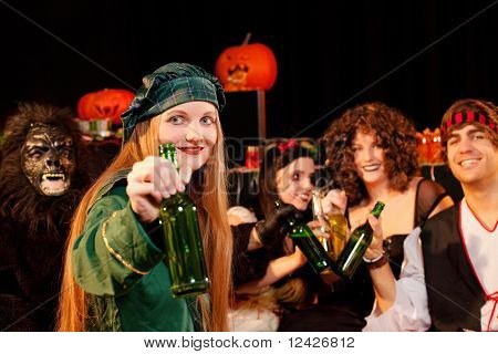 Group of young people celebrating a carnival or Halloween party in costumes drinking beer