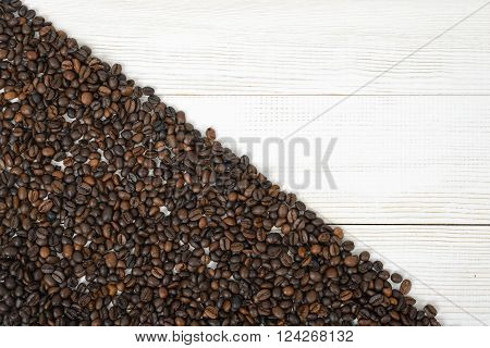 A wooden surface half backfilled with coffee beans on diagonally