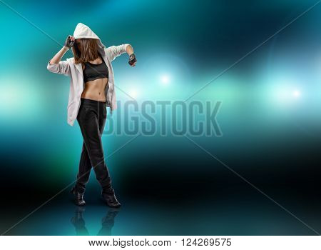 Girl dancer wearing hoodie stands on tiptoe raising her hands, on a flashing green background