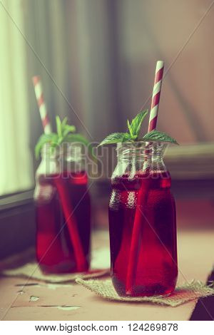 Two jars with organic raspberry juice placed on a burlap coasters with two striped red and white drinking straws and fresh mint leaves in it placed on a restaurant table next to a window