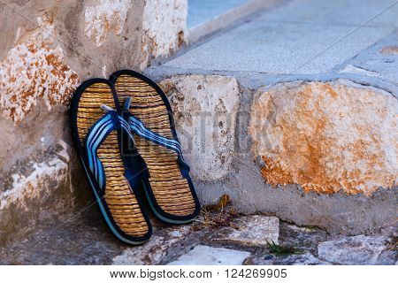 Beach flip-flops on the old wall background. Horizontal shot