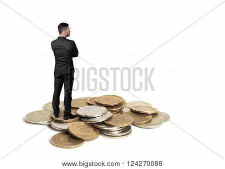 Back view of cutout businessman in a black suit with folded arms standing on a copper heap of ruble coins
