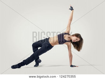 Young beautiful girl dancer wearing sport clothes in position arm balance with addition reliance on her leg