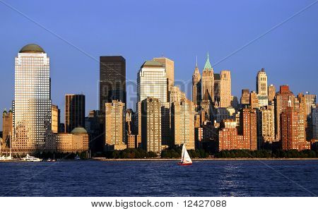 Lower Manhattan in New York City and sunset with red sailboat