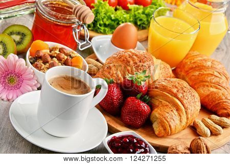 Breakfast consisting of croissants coffee fruits orange juice coffee and jam. Balanced diet.
