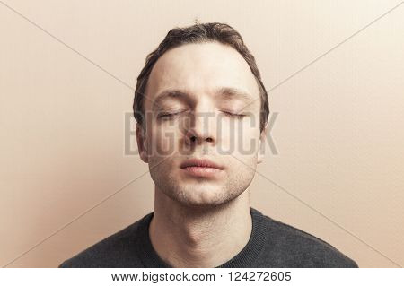 Young Caucasian man with closed eyes. Studio portrait over gray wall background, old style photo filter tonal correction effect