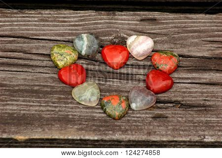 Jasper, unakite and fluorite hearts set laying on a wooden background ** Note: Soft Focus at 100%, best at smaller sizes