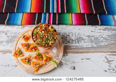 Nachos chips and vegetables in an earthenware bowl tequila lime salt and poncho seen from above