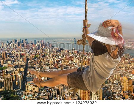 Happy and young woman with shorts, shirt and wide-brimmed hat swinging on the New York skyline background. Freedom concept.