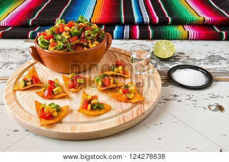 Nachos chips and vegetables in an earthenware bowl and tequila with a poncho on background over a wooden table