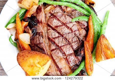 ethically raised fresh cut organic rib eye steak grilled rare with fresh roasted vegetables