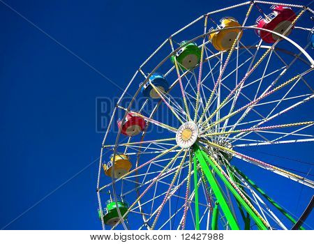 View of a still ferris wheel on a sunny day at a carnival.