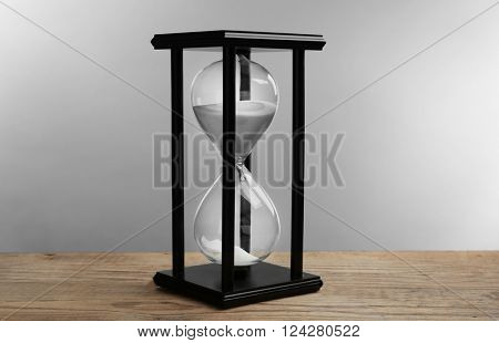 Black hourglass on wooden table, close up