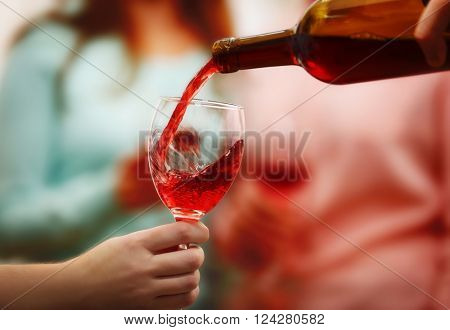 Pouring red wine into glass at hen-party, close up