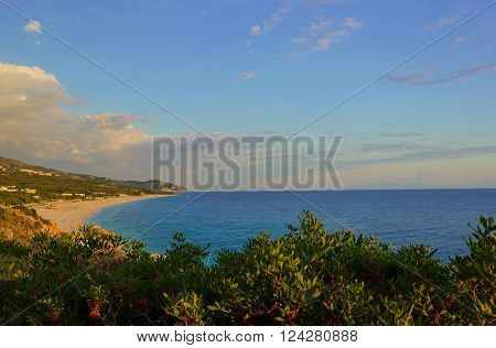 Summer Ionian Sea coastline view with sandy beach on the sunset with green bushes in front, Albania