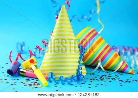 Two Birthday hats with serpentine streamer and noise makers on blue background