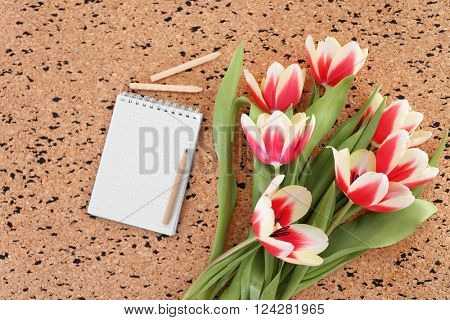 Bouquet of variegated tulips with notebook and pens on pin board