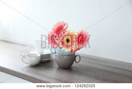 Bouquet of pink gerberas with dishware on wooden table