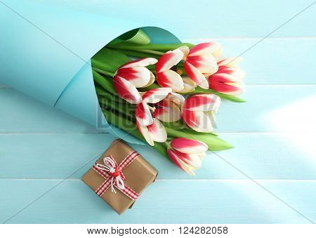 Bouquet of variegated tulips wrapped in paper with gift box on blue wooden background