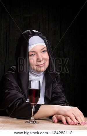 Portrait of beautiful young nun sitting at a wooden table with a glass of red wine