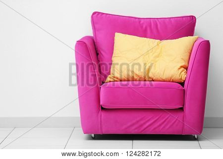 Pink armchair with yellow pillow on white wall background