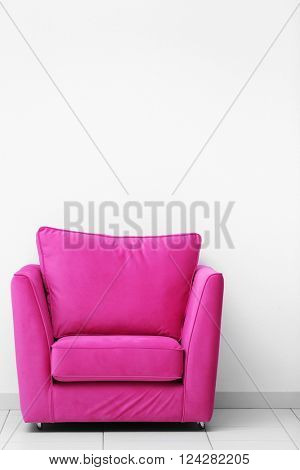 Pink armchair on white wall background