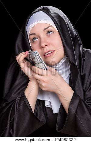 Joyous nun pressed her face to the money and looking up isolated on a black background