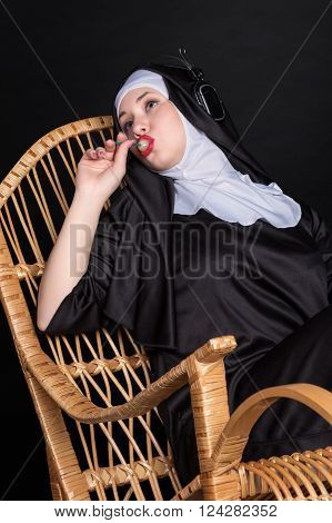 Nun sitting in a rocking chair sucking candy and listening to music on headphones